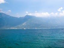 Ansicht zum See Garda mit einer Fähre und zahlreichen kleinen Booten im Abstand Lizenzfreies Stockbild