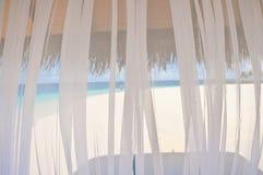 Ansicht zum weißen tropischen Strand durch transparenten Fenstervorhang Stockfotografie