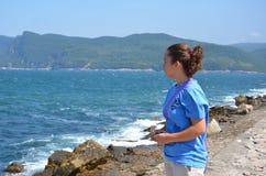 Ansichten, die das Meer und die Schönheit des Mädchens übersehen Lizenzfreie Stockbilder