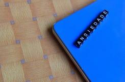 Ansiedade的概念用木立方体的葡萄牙语与书在背景中 库存照片