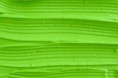 Ansikts- maskering för grön kosmetisk lera, kräm- texturslut upp, selektiv fokus Abstrakt elektrisk bakgrund för limefruktgräspla Fotografering för Bildbyråer
