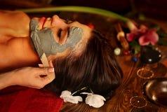 Ansikts- maskering för gyttja av kvinnan i brunnsortsalong Närbild av en ung kvinna som får Spa behandling royaltyfri fotografi