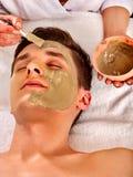 Ansikts- maskering för gyttja av kvinnan i brunnsortsalong Närbild av en ung kvinna som får Spa behandling arkivfoto