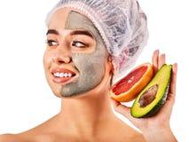 Ansikts- maskering för gyttja av kvinnan i brunnsortsalong Närbild av en ung kvinna som får Spa behandling arkivbild