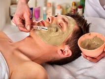 Ansikts- maskering för gyttja av mannen i brunnsortsalong Närbild av en ung kvinna som får Spa behandling royaltyfri foto
