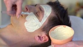 Ansikts- maskering för gyttja av mannen i brunnsortsalong Närbild av en ung kvinna som får Spa behandling lager videofilmer