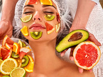 Ansikts- maskering från nya frukter för kvinna Kosmetologen applicerar skivor Royaltyfri Bild