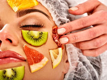 Ansikts- maskering från nya frukter för kvinna Kosmetologen applicerar skivor Arkivfoto