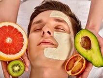 Ansikts- maskering från nya frukter för man Kosmetologen applicerar skivor Arkivbild