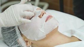 Ansikts- maskering som applicerar genom att använda borsten i skönhetsalong Spa kosmetolog som applicerar ansiktsbehandlingen som arkivfilmer