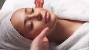 Ansikts- massage för Spa kvinna Framsidamassage i skönhetbrunnsortsalong Kvinnlig som tycker om avslappnande framsidamassage i co lager videofilmer