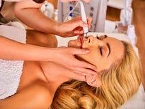 Ansikts- massage på skönhetsalongen Elektrisk omsorg för stimulanskvinnahud arkivfoton