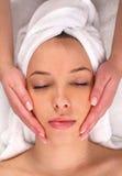ansikts- massage som mottar kvinnan royaltyfria foton