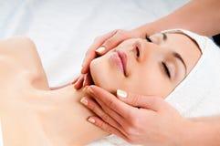 ansikts- massage som mottar kvinnan royaltyfri foto