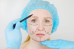 Ansikts- plastikkirurgi eller facelift, facelift, framsidakorrigering En plast- kirurg undersöker en patient för plastikkirurgi royaltyfri fotografi
