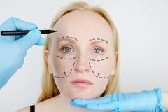 Ansikts- plastikkirurgi eller facelift, facelift, framsidakorrigering En plast- kirurg undersöker en patient för plastikkirurgi royaltyfri foto