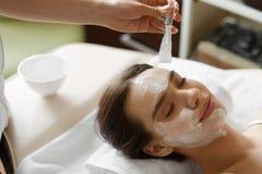 Ansikts- skönhetbehandling Härlig kvinna som får den kosmetiska maskeringen Royaltyfria Foton
