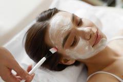 Ansikts- skönhetbehandling Härlig kvinna som får den kosmetiska maskeringen Royaltyfria Bilder
