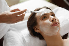 Ansikts- skönhetbehandling Härlig kvinna som får den kosmetiska maskeringen Arkivfoto