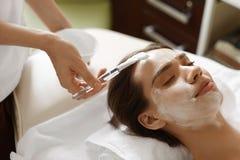 Ansikts- skönhetbehandling Härlig kvinna som får den kosmetiska maskeringen Fotografering för Bildbyråer