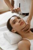 Ansikts- skönhetbehandling Kvinna som får syrehudskalning Arkivfoto