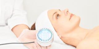Ansikts- tillvägagångssätt för Skincare cosmetology kvinna f?r smink f?r sk?nhetframsidamode Blå ljus medicinsk terapi Specialist arkivbilder
