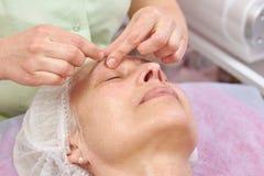 ansiktsbehandling som har den mogna kvinnan för massage Royaltyfria Foton