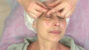 ansiktsbehandling som har den mogna kvinnan för massage stock video