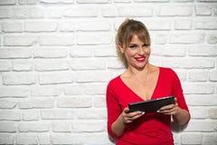 Ansiktsuttryck av den unga blonda kvinnan på tegelstenväggen Royaltyfria Foton
