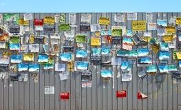 Anslagstavla på metallstaketet med färgglade meddelanden på gatan royaltyfri bild