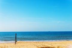 Ansluta pilings på en sandig strand, ett blått hav och en gul sand som är soliga Fotografering för Bildbyråer
