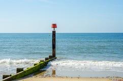 Ansluta pilings på en sandig strand, ett blått hav och en gul sand som är soliga Arkivfoto