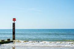 Ansluta pilings på en sandig strand, ett blått hav och en gul sand som är soliga Royaltyfria Foton
