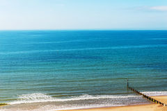 Ansluta pilings på en sandig strand, ett blått hav och en gul sand som är soliga Arkivbilder