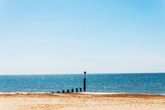 Ansluta pilings på en sandig strand, ett blått hav och en gul sand som är soliga Royaltyfri Bild