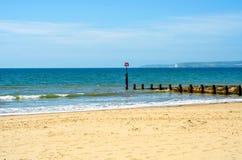 Ansluta pilings på en sandig strand, ett blått hav och en gul sand som är soliga Arkivbild