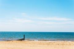 Ansluta pilings på en sandig strand, ett blått hav och en gul sand som är soliga Arkivfoton