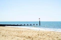 Ansluta pilings på en sandig strand, ett blått hav och en gul sand som är soliga Royaltyfria Bilder