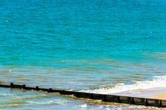 Ansluta pilings på en sandig strand, ett blått hav och en gul sand som är soliga Royaltyfri Fotografi