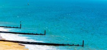 Ansluta pilings på en sandig strand, ett blått hav och en gul sand som är soliga Royaltyfri Foto