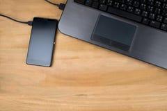 Anslutningen av den svarta mobiltelefonen och svartdatoren Arkivbilder