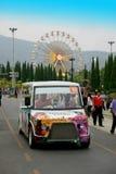 Anslutningsbuss med färgrik bakgrund för ferrishjul Royaltyfri Foto