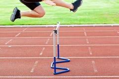 Anspruchsvoller männlicher Athlet, der über eine Hecke springt Lizenzfreies Stockbild