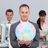 Anspruchsvoller Manager, der an der globalen Dynamicdehnung lächelt Lizenzfreie Stockfotos