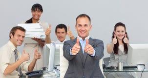 Anspruchsvoller Manager und sein Team mit den Daumen oben Lizenzfreie Stockfotos