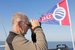 Anställd med kikare sänder som seglar till Natuurmonumenten Griend Arkivbild