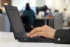 Anställd räcker arbete i kontoret Arkivbild