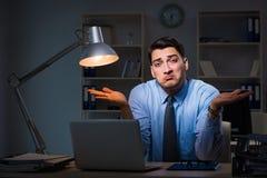 Anställd som sent arbetar på natten på den viktiga rapporten Royaltyfri Bild