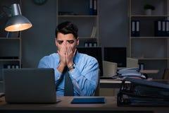 Anställd som sent arbetar på natten på den viktiga rapporten Arkivbild