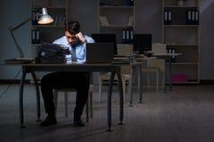 Anställd som sent arbetar på natten på den viktiga rapporten Royaltyfria Bilder